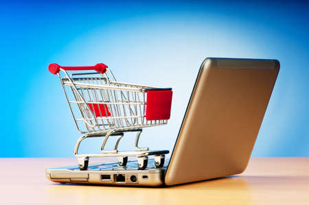 merchandise: Internet online shopping concept with computer and cart Stock Photo
