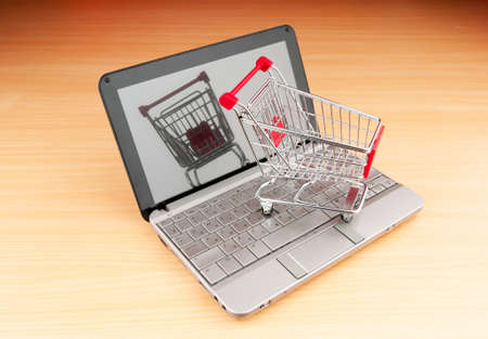 Internet online shopping concept with computer and cart Stock Photo - 9716746