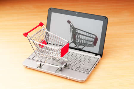 Internet online shopping concept with computer and cart Stock Photo - 9752903