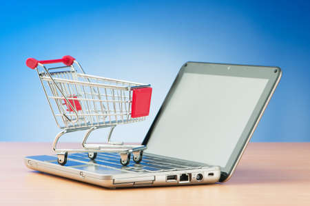 Internet online shopping concept with computer and cart Stock Photo - 9752978