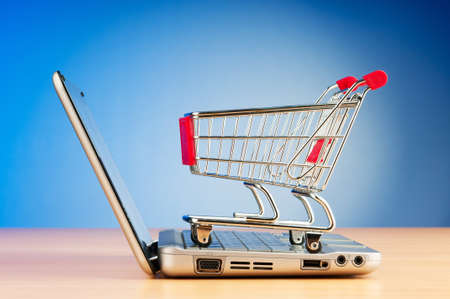 Internet online shopping concept with computer and cart Stock Photo - 9752886