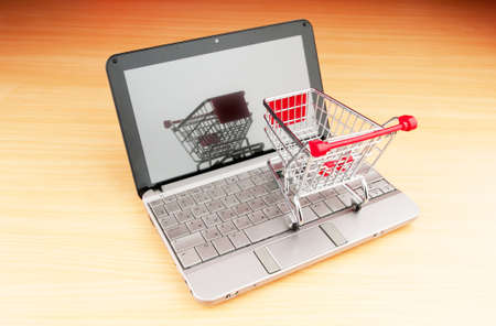 Internet online shopping concept with computer and cart Stock Photo - 9752942