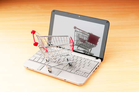 Internet online shopping concept with computer and cart Stock Photo - 9822866