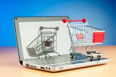 Internet online shopping concept with computer and cart Stock Photo - 9822873