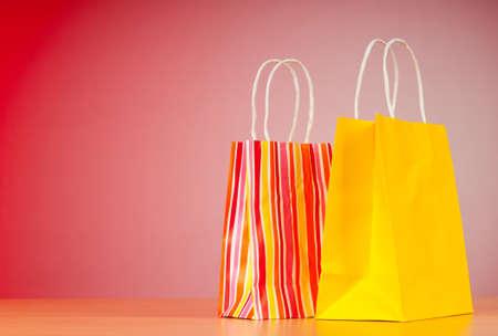 グラデーションの背景にカラフルな紙のショッピング バッグ 写真素材