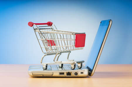 Internet online shopping concept with computer and cart Stock Photo - 9847606