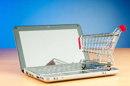 Internet online shopping concept with computer and cart Stock Photo - 9847719