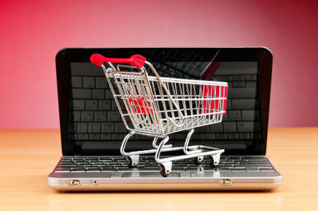 Internet online shopping concept with computer and cart Stock Photo - 9847568