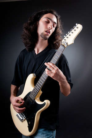 Guitar player against the dark background photo