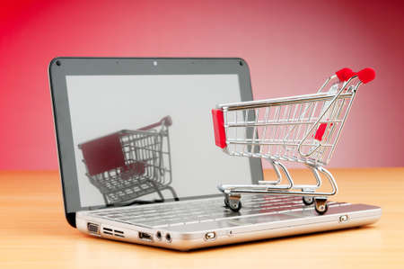 Internet online shopping concept with computer and cart Stock Photo - 9917864