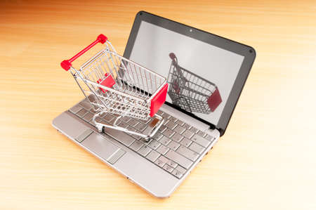 Internet online shopping concept with computer and cart Stock Photo - 10132370