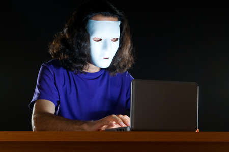 Hacker sitting in dark room Stock Photo - 10619855