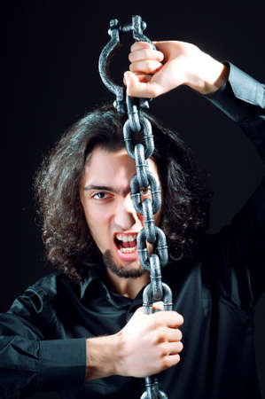 Man chained in the dark room Stock Photo