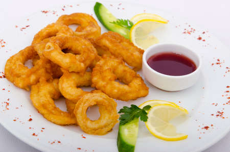 Fried calamari rings served with sauce photo