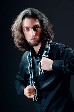 Man chained in the dark room Stock Photo - 14385961