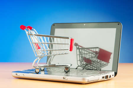 Shopping online with computer and cart photo