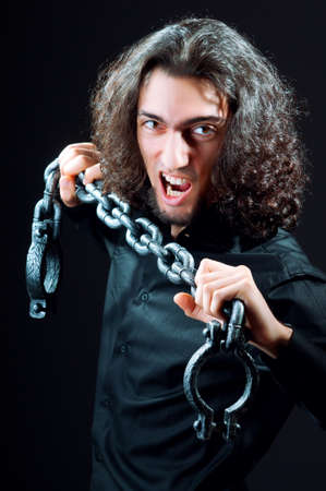 Man chained in the dark room Stock Photo - 10925286