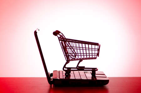 Silhoette of shopping cart and laptop photo