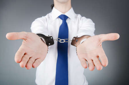Businessman handcuffed for his crimes photo
