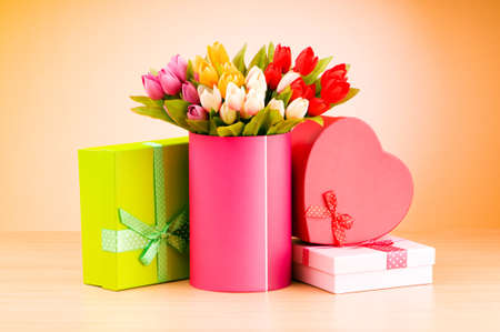 Giftbox and tulips against gradient background photo