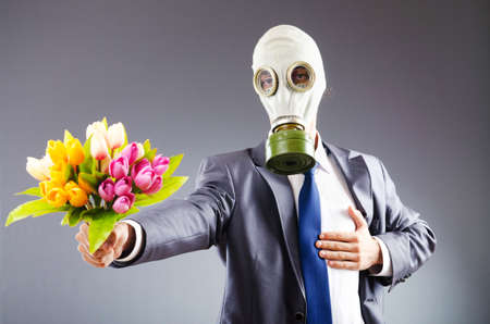 Businessman with gas mask and flowers photo