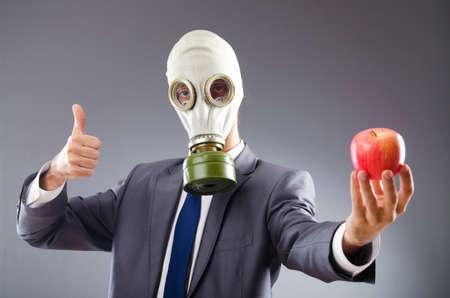 sustancias toxicas: Hombre de negocios con máscara de gas y la manzana Foto de archivo