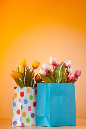 Tulips in the bag against gradient background photo