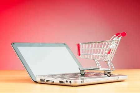 consumerism: Shopping online with computer and cart
