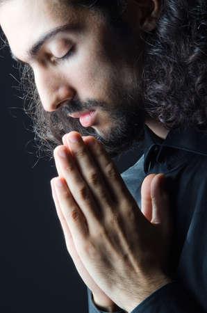 hombre orando: Hombre joven rezando en la oscuridad Foto de archivo