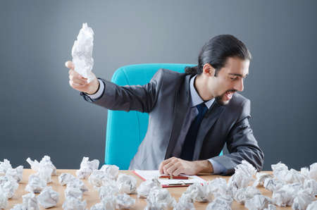 Businessman with lot of discarded paper photo