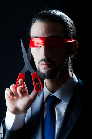 Man cutting ribbon on his eyes photo
