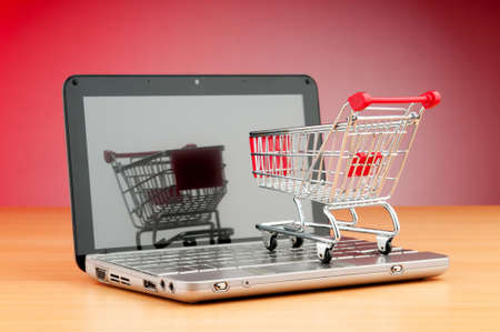 Internet online shopping concept with computer and cart Imagens
