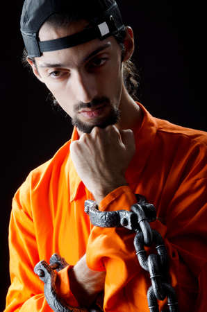 an inmate: Inmate chained on black background Stock Photo
