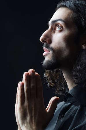 alabando a dios: El hombre joven orando en la oscuridad