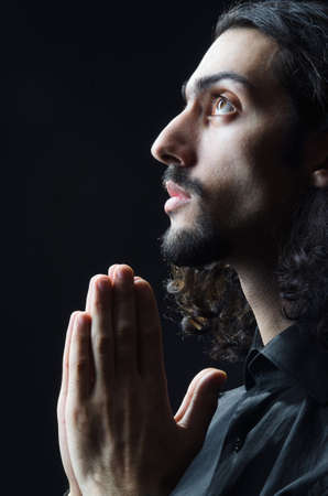 jesus face: Young man praying in darkness