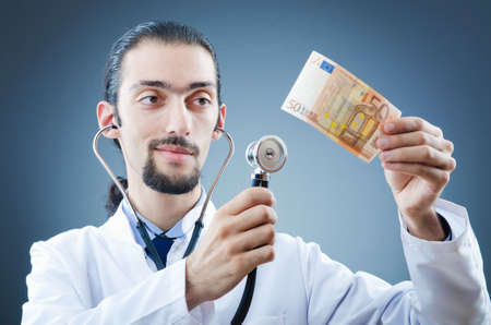 hospital fees: Doctor with money in studio