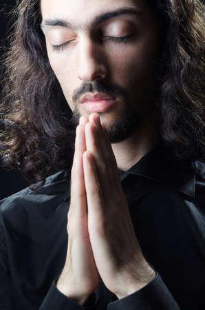 jesus face: Young man praying in darkness