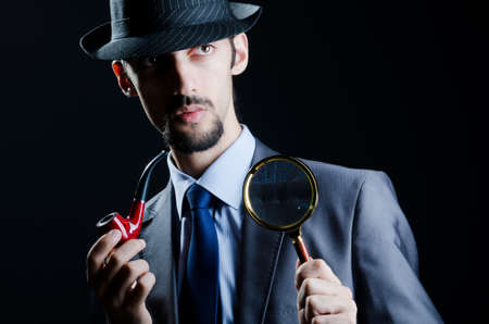 inquiring: Detective with magnifying glass and pipe Stock Photo