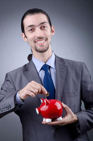 Man with piggybank on grey photo