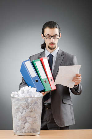 Man with lots of wasted paper photo