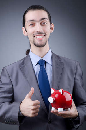 Man with piggybank on grey photo