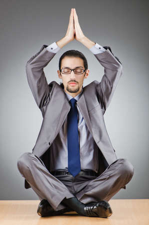 Businessman meditating sitting on the desk photo