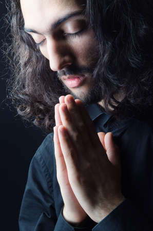 Young man praying in darkness photo
