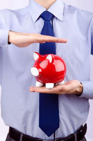 Man saving his money in the piggybank Stock Photo - 12345667