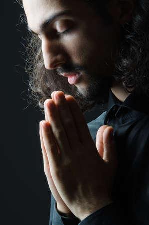 stil zijn: Jonge man, die bidt in de duisternis Stockfoto