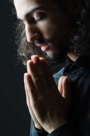 Young man praying in darkness Stock Photo - 12556502