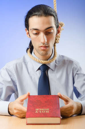 Businessman reading bible before hanging himself photo