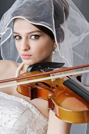 Bride playing violin in studio photo