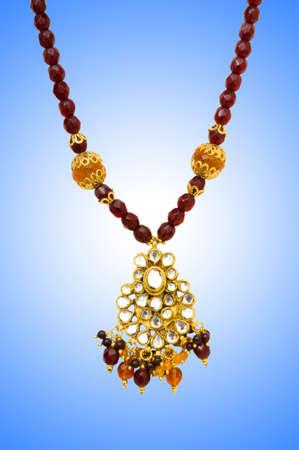 Golden jewellery against gradient background photo
