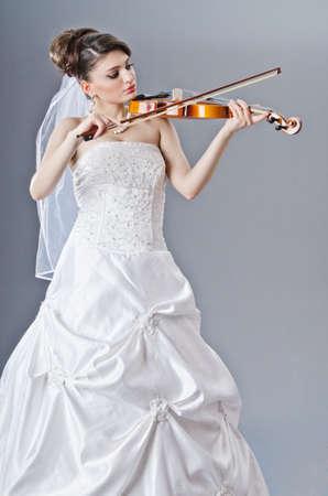 Bride playing violin in studio photo